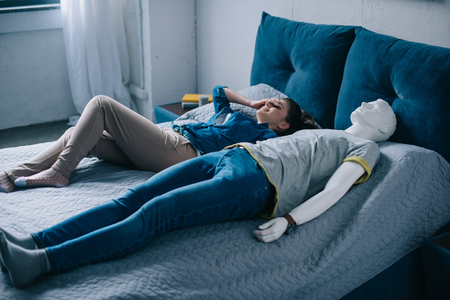 young woman lying in bed with mannequin, perfect relationship dream concept Zdjęcie Seryjne
