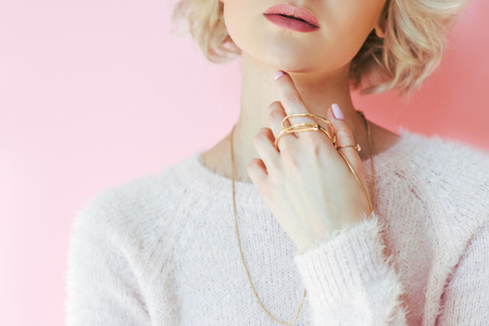 cropped shot of sensual young woman holding jewelry in hand isolated on pink