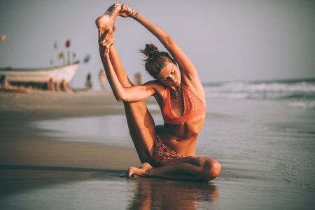young flexible woman in swimsuit practicing yoga on beach at goa Stock Photo - 114325942