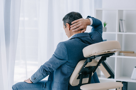 adult businessman with painful backache sitting in massage chair at office Stockfoto