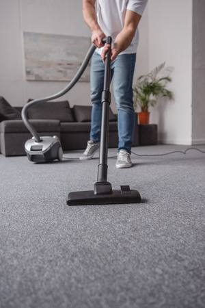 cropped image of man vacuuming carpet in living room 스톡 콘텐츠