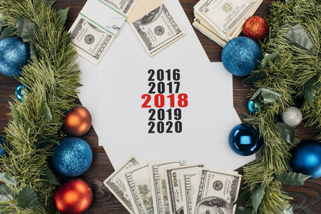 flat lay with money, christmas decorations and calendar on wooden tabletop Stock Photo