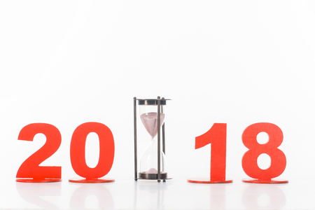 close up view of sand clock and 2018 year sign isolated on white