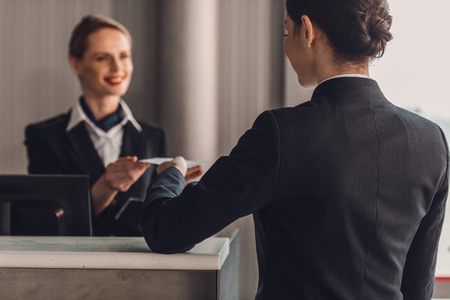 rear view of businesswoman giving ticket to staff at airport check in counter Stockfoto