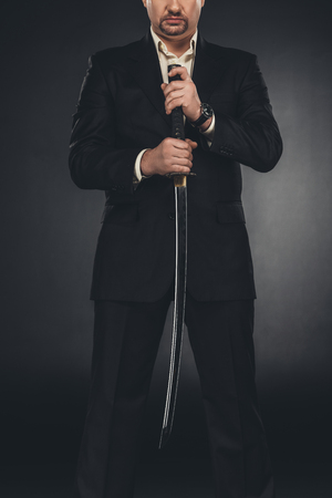 cropped shot of yakuza member in suit holding katana sword on black