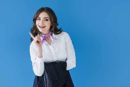 smiling beautiful stewardess showing one finger isolated on blue Foto de archivo