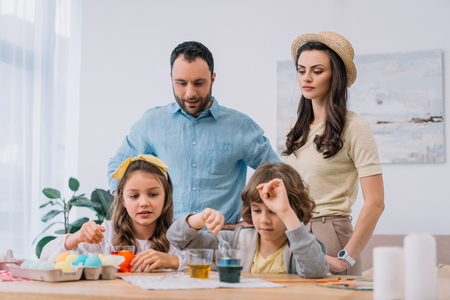 young family painting eggs for easter holiday at home Stock Photo