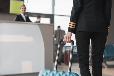 cropped shot of female pilot with suitcase at airport lobby