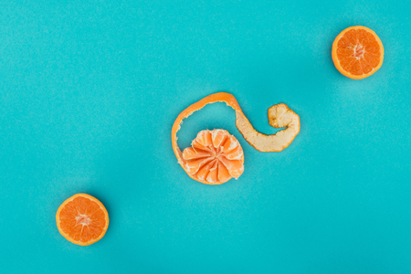 top view of arranged ripe mandarin and orange pieces isolated on blue