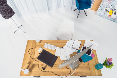 Top view of table of designer with fashion illustrations and computer 스톡 콘텐츠