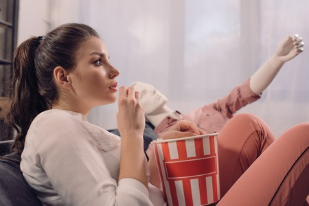 woman eating popcorn while watching film together with manikin at home, perfect relationship dream concept Foto de archivo