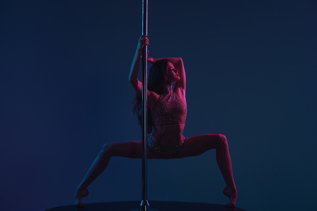 full length view of beautiful flexible young woman dancing with pole on blue Banco de Imagens - 114326171