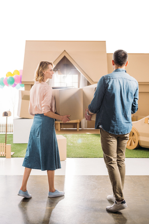 rear view of couple moving into new cardboard house isolated on white
