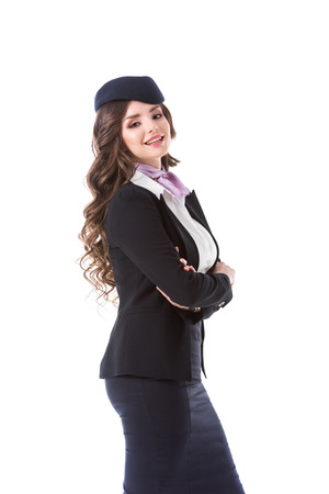 side view of attractive stewardess with crossed arms isolated on white Foto de archivo