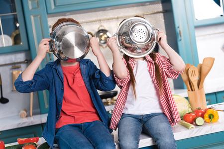 cute little children having fun with utensils in kitchen
