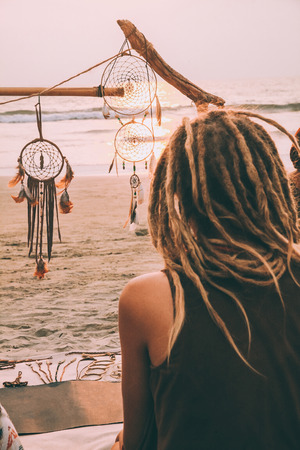 back view of young person sitting on beach and looking at sunset and dreamcatchers in goa