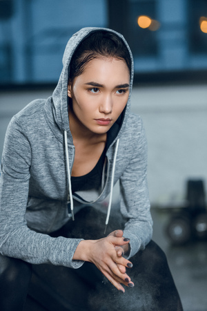young fit woman clapping hands with talc before workout at gym Stock Photo