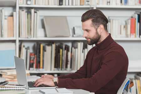 side view of handsome student using laptop in library