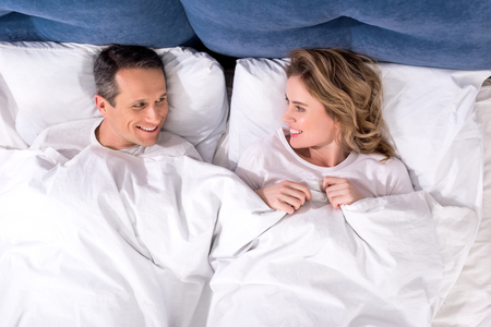 overhead view of smiling wife and husband lying in bed at home Standard-Bild - 114326421