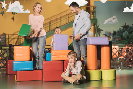 bored little boy sitting on floor while happy family playing with blocks in entertainment center Stockfoto