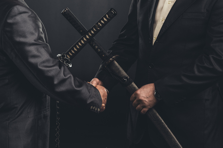 cropped shot of meeting of yakuza members in suits with katana swords isolated on black Stock Photo