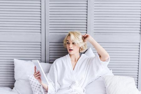 beautiful surprised girl in bathrobe using digital tablet on bed