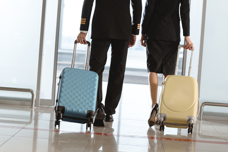cropped shot of pilot and stewardess with suitcases walking by airport Stockfoto