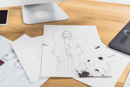 Work table of designer with fashion illustrations and computer