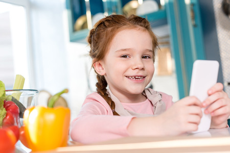 adorable child smiling at camera while using smartphone in kitchen