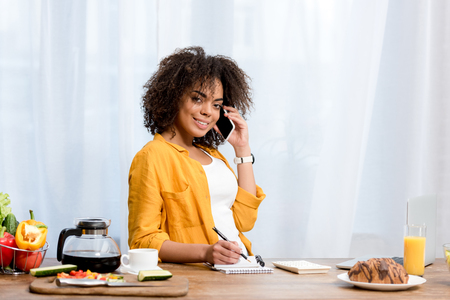 smiling young woman talking by phone at kitchen and looking at camera