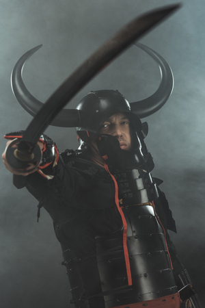 close-up shot of samurai in traditional armor with katana sword on dark background with smoke