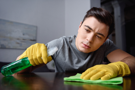 handsome man cleaning table in living room with spray bottle and rag