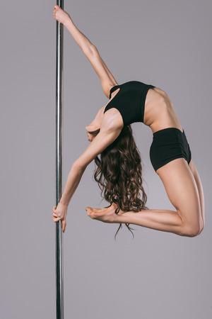 young flexible pole dancer in sportswear training on grey Standard-Bild - 114326554