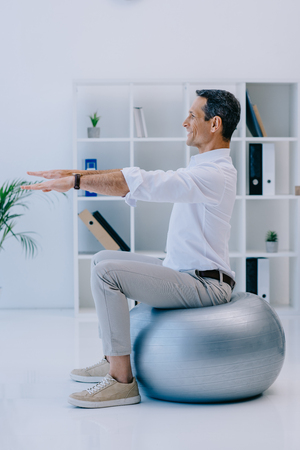 happy mature businessman balancing on fit ball at office