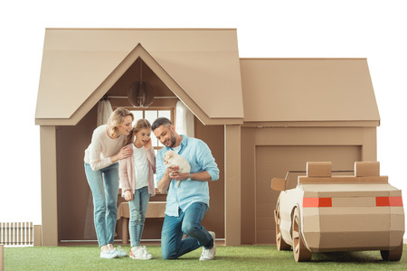 beautiful family with adorable labrador puppy in front of cardboard house isolated on white Stock fotó