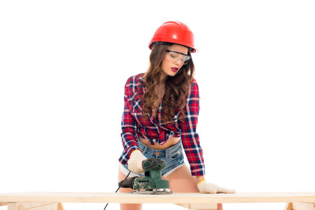sexy girl in hardhat working with grind tool at wooden table, isolated on white