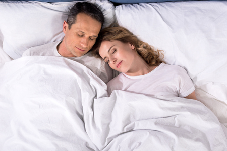 overhead view of couple sleeping in bed at home