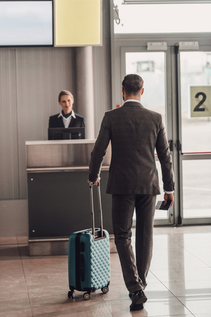 rear view of businessman walking to airport check in counter