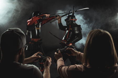 rear view of man and woman playing samurai fighting in real life with gamepads on black Stok Fotoğraf - 114326791