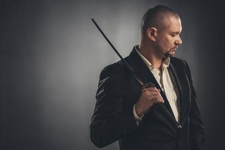 thoughtful man in suit with katana sword on black Stock Photo