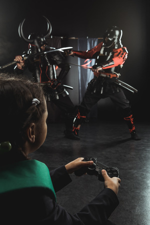 schoolchild playing samurai fighting with gamepad in real life Stock Photo