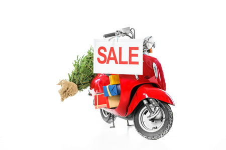 christmas tree and presents on red scooter with sale sign, isolated on white Stok Fotoğraf