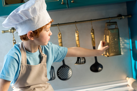 adorable little boy in chef hat and apron looking at utensils while sitting in kitchen