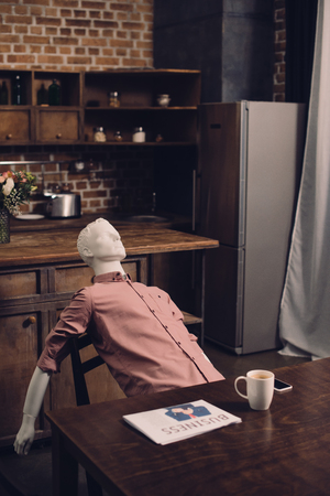 close up view of manikin at table with cup of coffee and newspaper in kitchen