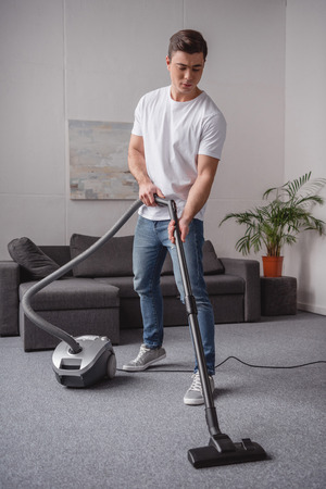 handsome  man cleaning carpet in living room with vacuum cleaner 스톡 콘텐츠