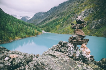 pile of stones near beautiful lake in majestic mountains, Altai, Russia