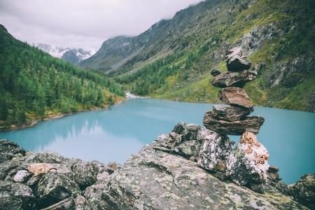 Steinhaufen in der Nähe von schönem See in majestätischen Bergen, Altai, Russland