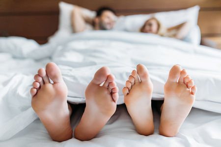boyfriend and girlfriend lying in bed with feet on foreground