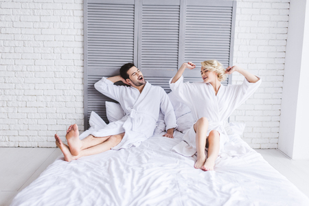 full length view of happy young couple in bathrobes stretching at morning in bed