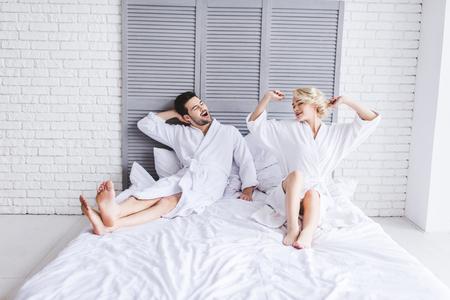 vista a tutta lunghezza di una giovane coppia felice in accappatoio che si allunga al mattino a letto